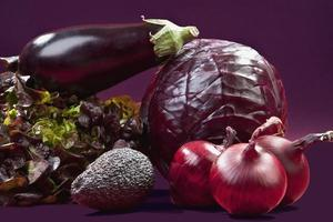 rå grönsaker mot lila bakgrund foto
