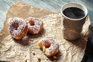 närbild av varmt kaffe och munkar på papper foto