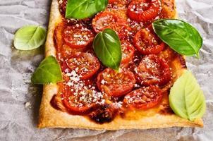 paj med tomater, ost och basilika foto
