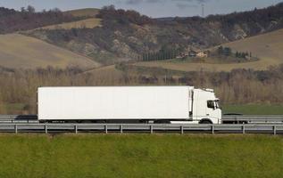 vit lastbil på motorvägen