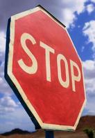 vägskylt stopp isolera på blå himmel foto
