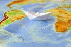 pappersbåt på en bakgrundskarta över världen foto