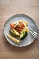tallrik med kokta potatis, broccoli, pickles, raclette och grillad bacon foto