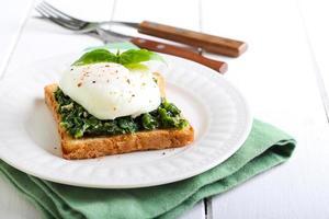 krämig spenat och pocherad äggrostat bröd foto