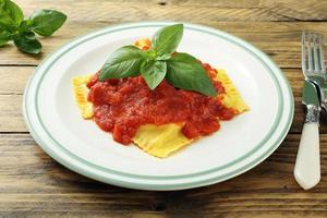 långsam mat ravioli med tomatsås foto
