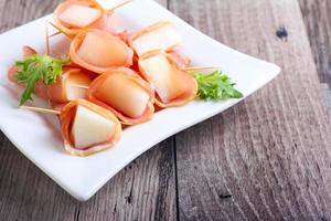 skivor melon inslagna med skinka foto