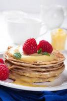 läckra pannkakor med lime ostmassa och hallon. foto