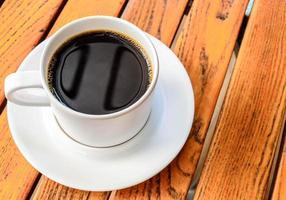 kaffekopp med på träbord, kaffepaus foto