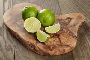 mogna limefrukter på olivbräda foto
