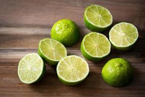 färska snitt limefrukter på träbakgrund foto