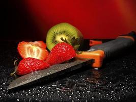 färska frukter med vattendroppar på dem och kniv foto