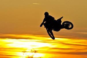motocross hoppar ner i solnedgången foto
