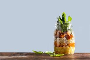 varm sallad från grillad pumpa, kikärter, morötter, quinoa och foto