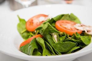 spenatsallad med skivade tomater