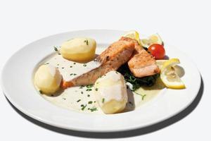 närbild av stekt lax med spenat, kokta potatis foto