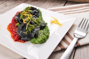 svart ravioli med spenat och vitlöksås tomat. foto