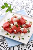 en vattenmelonfeta sallad på en fyrkantig vit platta foto