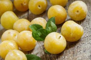 mogna gula plommon på gammal träbakgrund foto