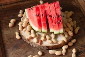 mogen röd vattenmelon med jordnötter på träbakgrund foto