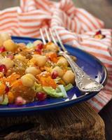 sallad med kikärter, russin, sesamfrön och grillad pumpa foto