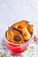 varm efterrätt med karamelliserade päron i röd kruka foto