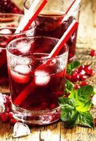färsk röd juice cocktail med granatäpplefrön, mynta och is foto