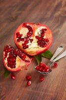 färsk mogen granatäpple med blad på ett träskiva. selektiv foto
