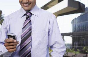 affärsman som använder mobiltelefon utomhus foto