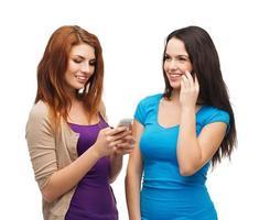 två leende tonårsflickor med smartphones foto