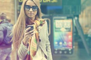 ung fashionabla kvinna med smartphone som går på gatan foto