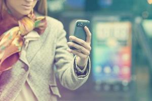 kvinnans hand med mobiltelefon foto
