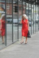 äldre kvinna pratar i mobiltelefon foto