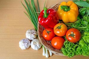 organiska grönsaker i rottingkorgen på träbakgrund foto