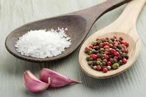 grovt salt, pepparkorn och vitlöksklyftor foto
