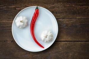 tallrik med röd varm chilipeppar och vitlök foto