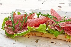 stor smörgås med salami, sallad och ruccola foto