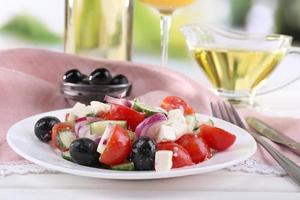 grekisk sallad serveras i tallrik med vin på bordet