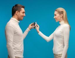 man och kvinna med smartphones foto