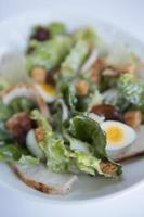 kyckling Caesar sallad med vaktlar ägg, pancetta och parmesan chips. foto