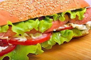 läckra färska smörgåsar med grön sallad, korv, tomater foto