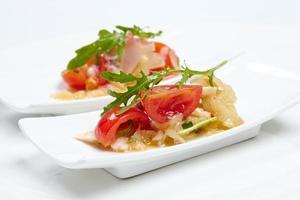 svenska bordrätter: tomater, ost, ruccola, bläckfisk, på foto