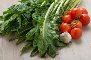 cikoria katalogna med tomater och vitlök på ett bord foto