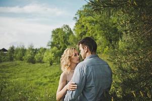 nygifta par i skogen om ett träd foto