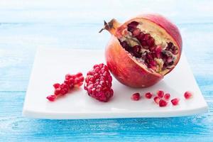 granatäpple på platta trä bakgrund foto