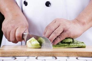 kock som skär grön sallad foto