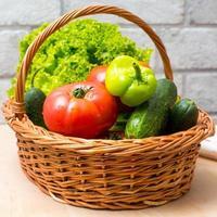 färska grönsaker i korg. tomat, gurka, peppar och sallad foto