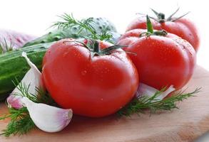 färska grönsaker: tomater, gurkor, vitlök och peppar foto