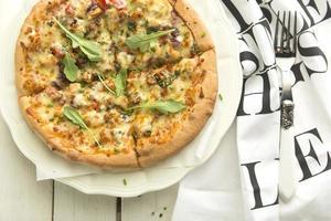 italiensk pizza på vit platta och vit bakgrund foto