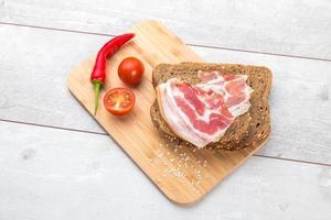 tomat, rostat bröd, kött på träbord foto