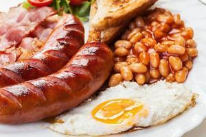 full engelsk frukost med bacon, korv, ägg och bakade bönor